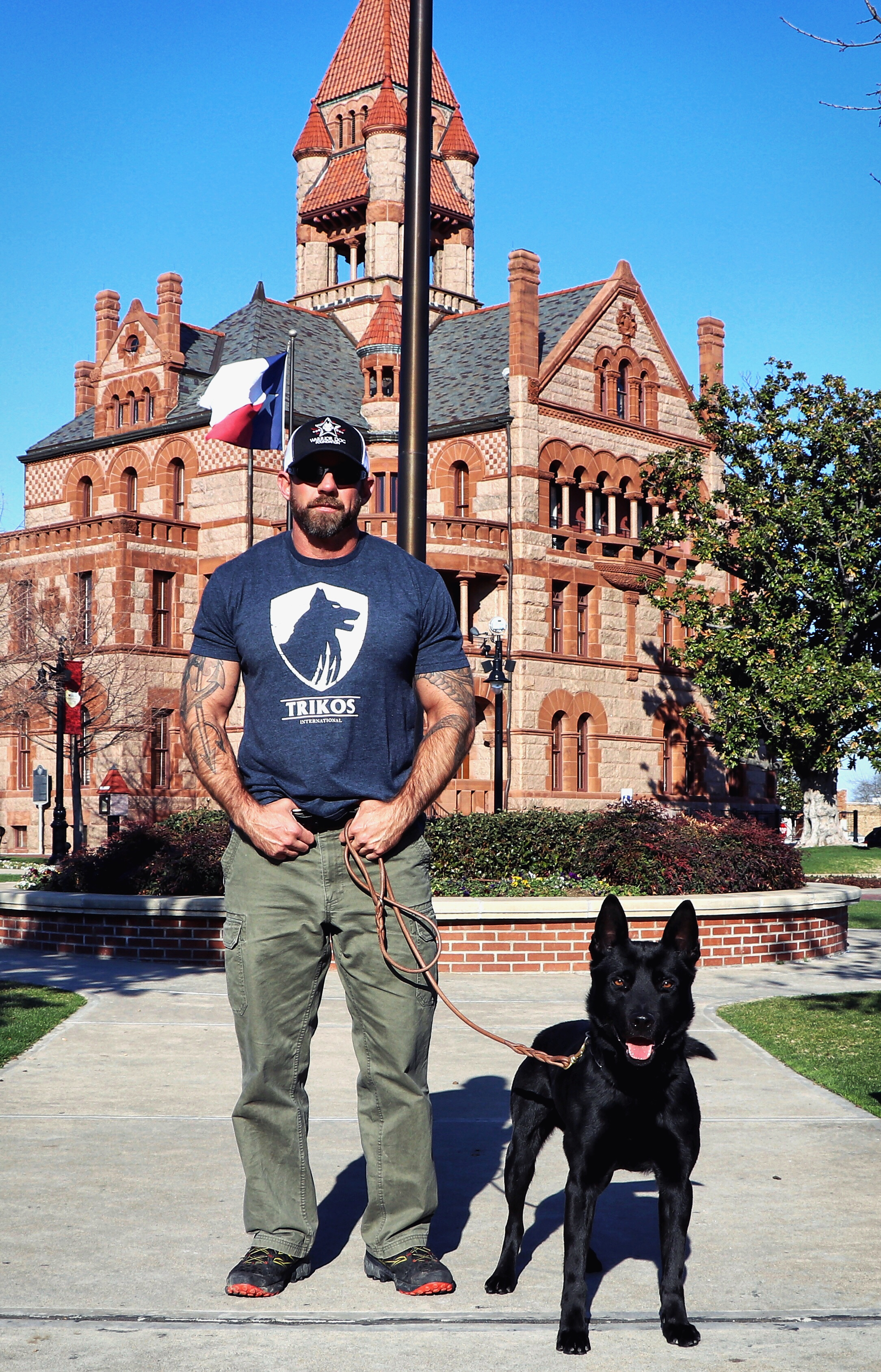 mike ritland with k9 dog in front of large house