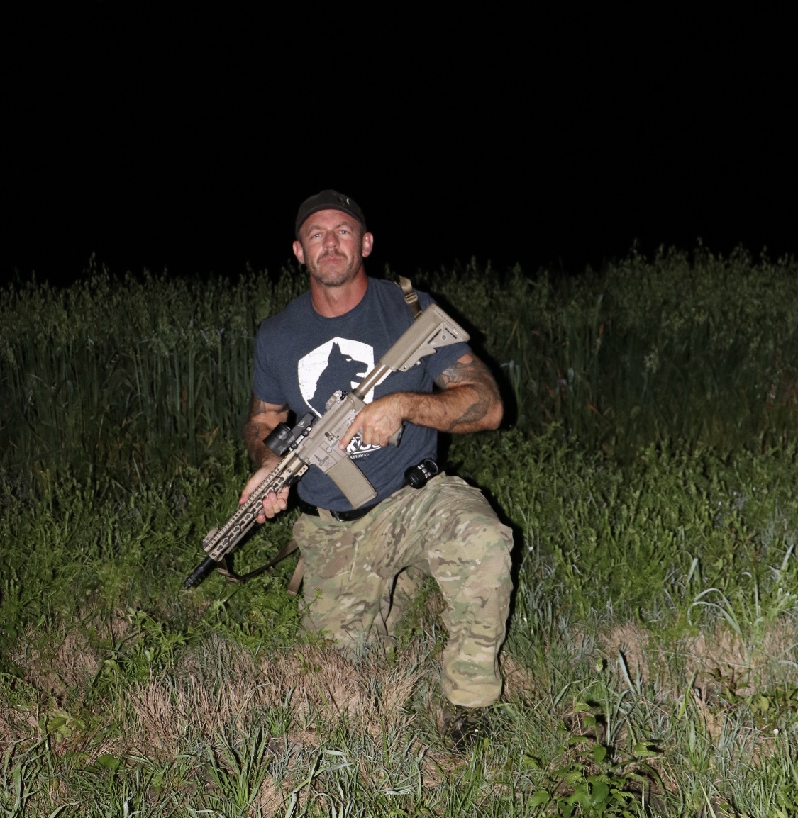 mike ritland with rifle in field at night